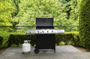 Horizontal photo of large barbeque cooker with lid up on concrete outdoor patio with woods background