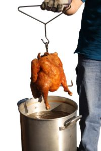 Deep fried turkey with a pot of oil isolated