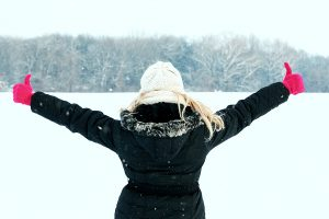winter woman in snow showing her back and facing forest with thumbs up hands raised high above copy space outside on cold winter day. Portrait Caucasian happy joyful female model with pink gloves and hat in first snow