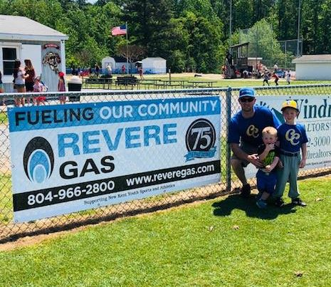 employee and two children posing in front of revere banner at park