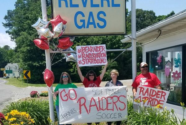 "employees posing under revere gas sign with ""go raiders"" banners"