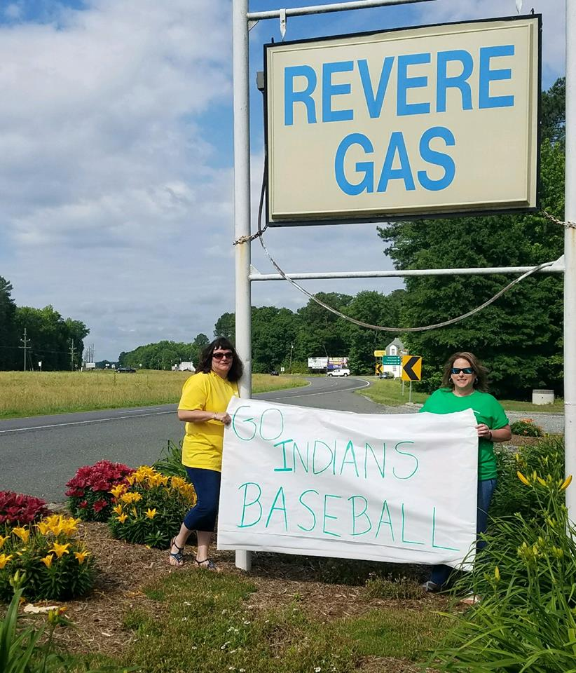"two employees posing under revere gas sign with ""go indians baseball"" banner"